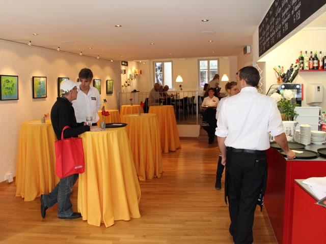 Menschen und Stehtische mit gelben Tischtüchern.