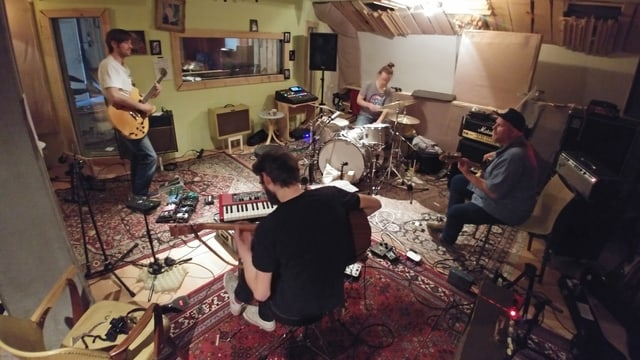Vier Musiker in schummrigem Bandlokal.