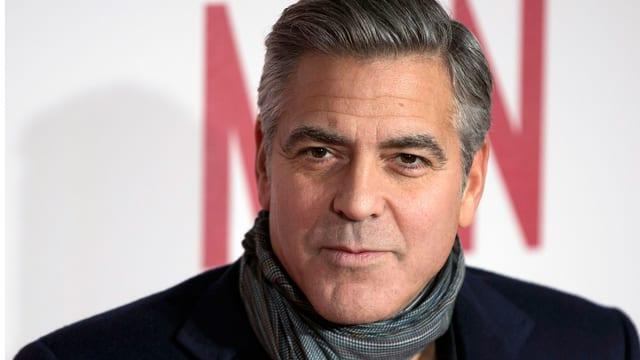George Clooney mit Schal blickt neutral in die Kamera.