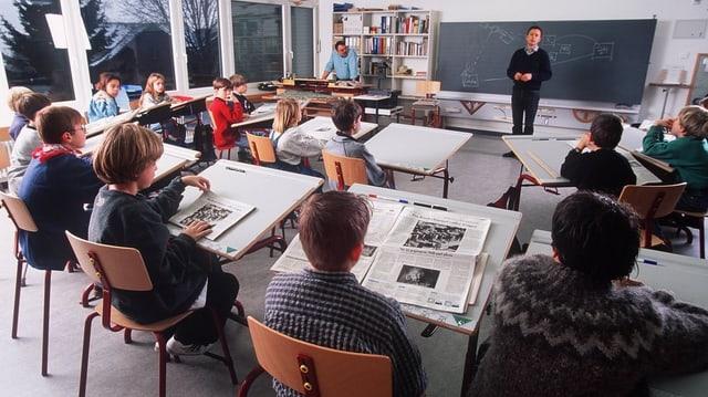 Ein Blick in eine Klassenzimmer mit jungen Schülern und dem Lehrer vor der Wandtafel.