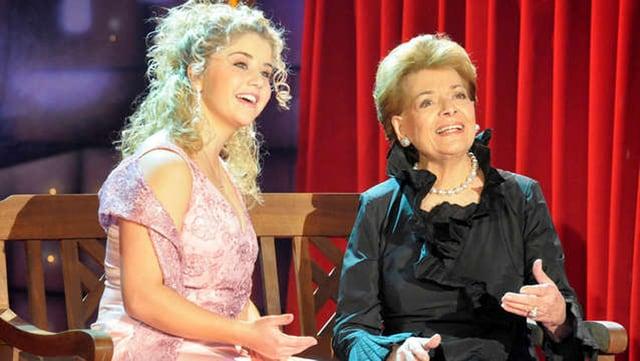 Zwei Sängerinnen auf Parkbank im TV.