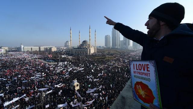 Menschenmassen vor einer Moschee, ein Mann auf einer Estrade zeigt mit dem Finger in die Ferne. Er hält ein Ich-liebe-Mohammed-Schild.