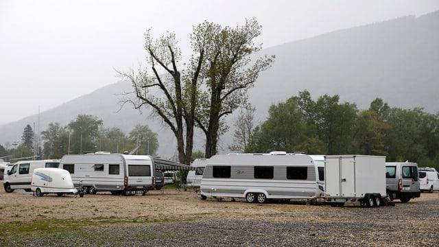 Mehrere Wohnwagen stehen auf einem Kiesplatz, im Hintergrund sind Bäume und ein Hügel.