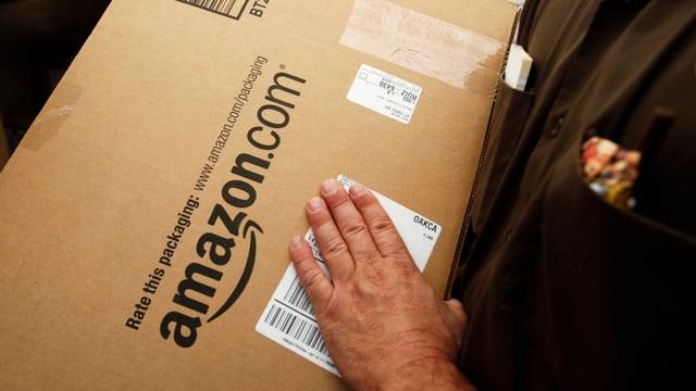 Ein Mann hält ein Paket von amazon.com in der Hand.