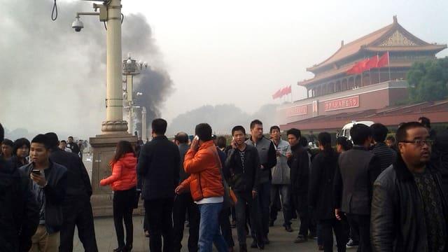 Menschen beobachten eine Rauchwolke in der Ferne, etliche von ihnen sind mit dem Handy am telefonieren.
