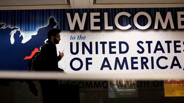 Mann läuft am Flughafen an einem Schild vorbei mit der Aufschrift: Willkommen in den vereinigeten Staaten von Amerika.