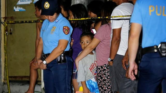 Eine Polizistin, rechts von ihr ein Junge hinter einer Absperrungsbanderole und andere Schaulustige.