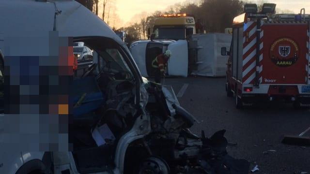 Im Vordergrund einer der Lieferwagen, im Hintergrund Einsatzfahrzeuge der Feuerwehr und der Rettungsdienste.