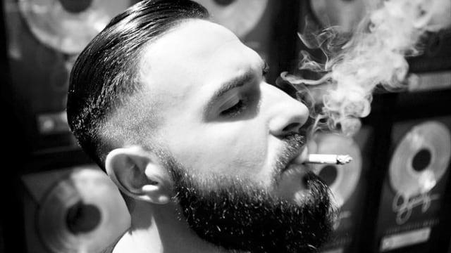 schwarzweiss seitenprofil eines bärtigen deutschen rappers mitzigarette