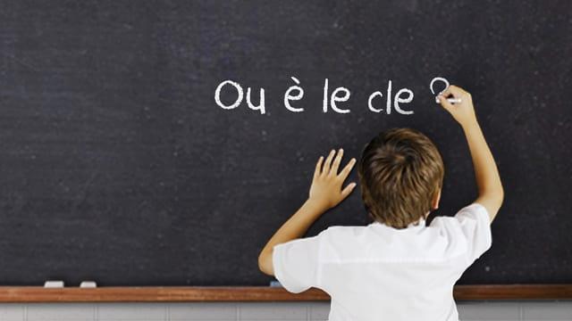 """Ein Junge schreibt den Satz """"ou è la cle?"""" an eine Wandtafel."""