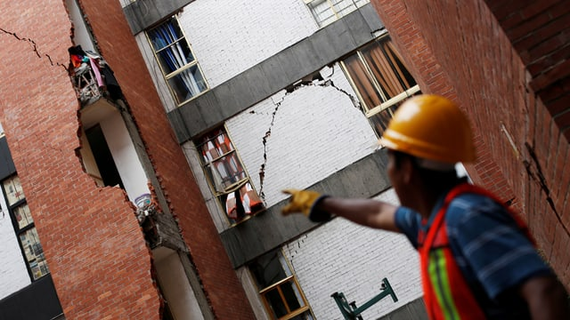 Arbeiter zeigt auf beschädigtes Gebäude