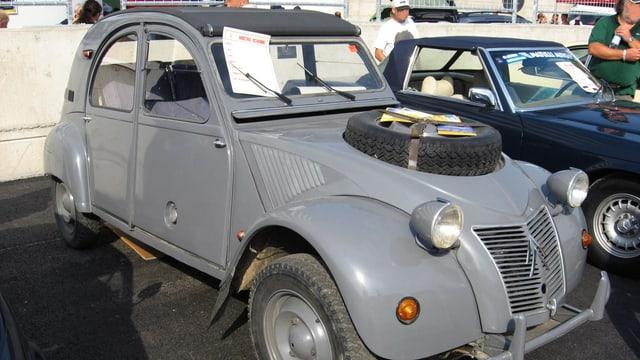 Ein grauer 2CV mit einem Rad auf der Kühlerhaube.