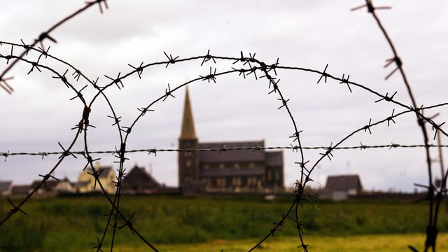 Die Kirche von Drumcree, aufgenommen durch einen Stacheldrahtzaun, mit dem die Strasse zur Kirche abgesperrt wurde.