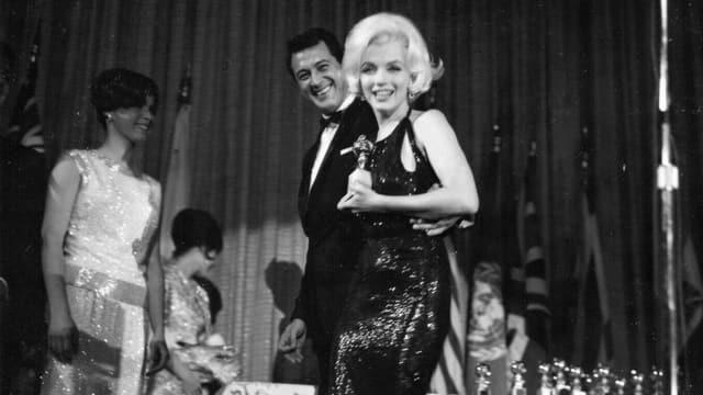 Marilyn Monroe hält ihren Golden Globe.