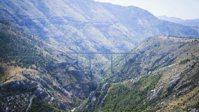 Die Moračabrücke mit langen Pfeilern steht zwischen grünen Hügeln.