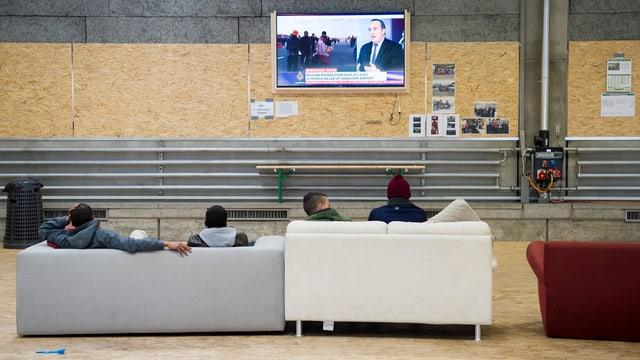Asylbewerber schauen in einer Halle Fernsehen.