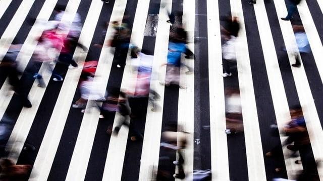 Menschen hetzen über einen schwarz-weiss-gestreiften Boden.