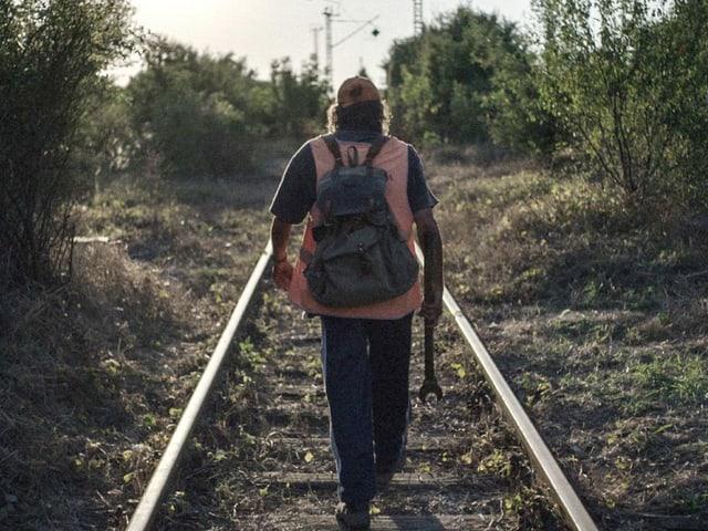 Ein Mann läuft auf einem Bahngleis entlang.