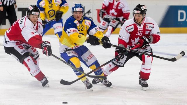 Ein Davoser Spieler kämpft sich gegen zwei Kanadier durch.