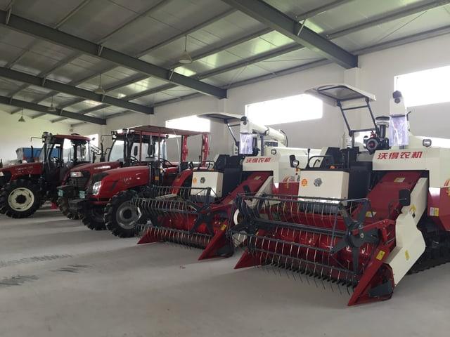 Moderne Traktoren und Mähmaschinen in einer Einstellhalle.