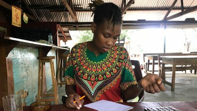 Eine schwarze Frau an einem Holztisch, auf dem sich ein Taschenrechner, Geldbündel und Glas Orangensaft befinden.