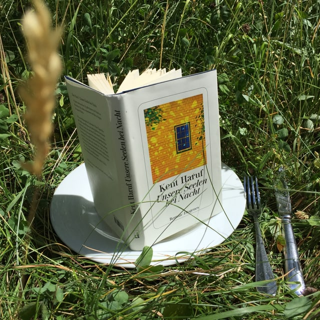 Das Buch «Unsere Seelen bei Nacht» von Kent Haruf steht aufrecht aufgeschlagen auf einem weissen Teller im Gras