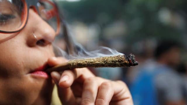 Junge Frau raucht einen Joint.
