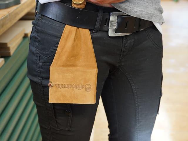 Ein hellbrauner Lederbeutel steckt unter einem schwarzen Ledergurt.
