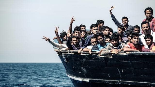 Menschen dichtegedrängt auf einem Holzkahn auf offenem Meer, manche winken mit den Händen.