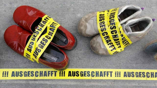 Schuhe, eingebunden mit einem Band mit der Aufschrift «Ausgeschafft» liegen auf dem Bundesplatz,