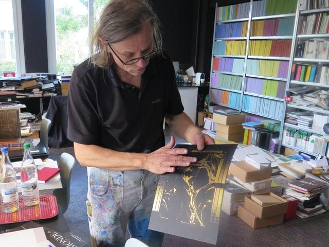 Lorenz Boegli in seinem Atelier mit einem Golddruck auf schwarzem Papier.