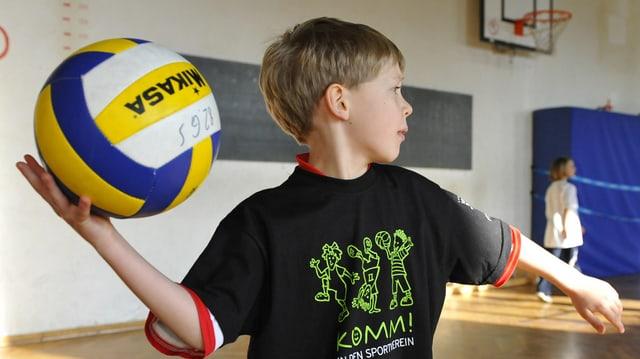 Ein Junge wirft einen Volleyball.