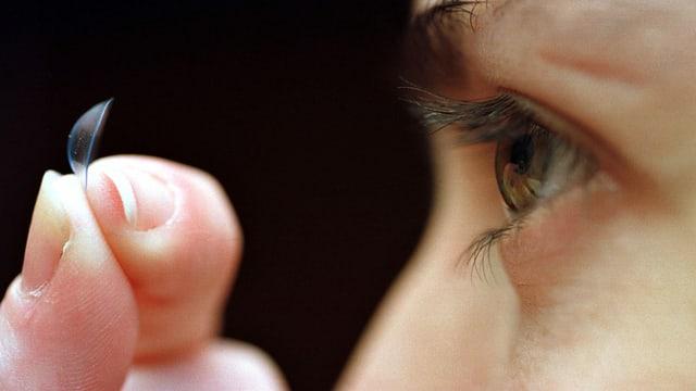 Eine Hand setzt eine Kontaktlinse ein.