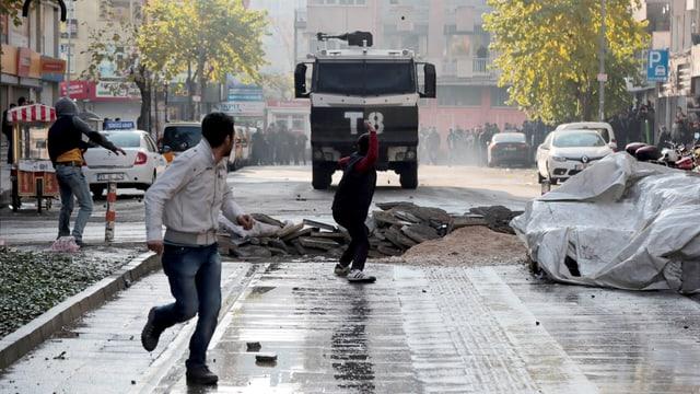 Zwei Männer hinter einer Strassenbarrikade rennen vor einem Tanklastwagen der Armee davon.