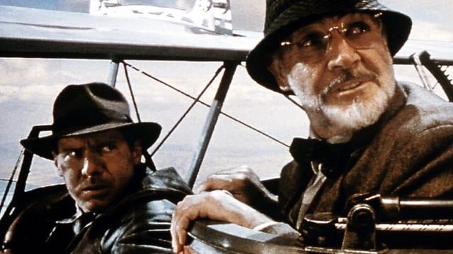Zwei Männer im Flugzeug - schauen beide rückwärts