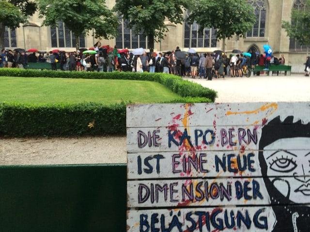 Ein Schild, dahinter Demonstranten.