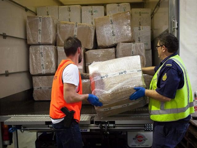 Zwei australische Beamte halten eine Kiste vor einem Container in den Händen