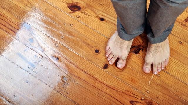 Mann steht barfuss auf einem Parkettboden.
