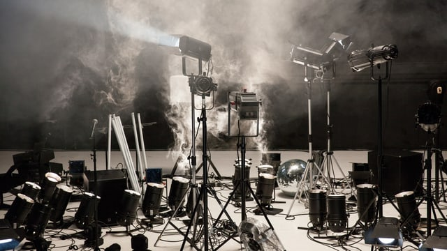 Auf einer Bühne stehen unzählige Scheinwerfer.