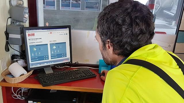 Mann blickt in den Computerbildschirm mit Wetterdaten.