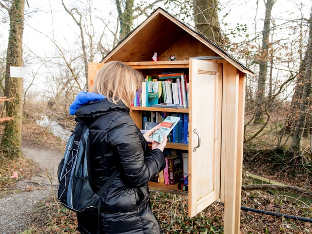 Frau nimmt ein Buch aus dem Bücherhäuschen im Wald.