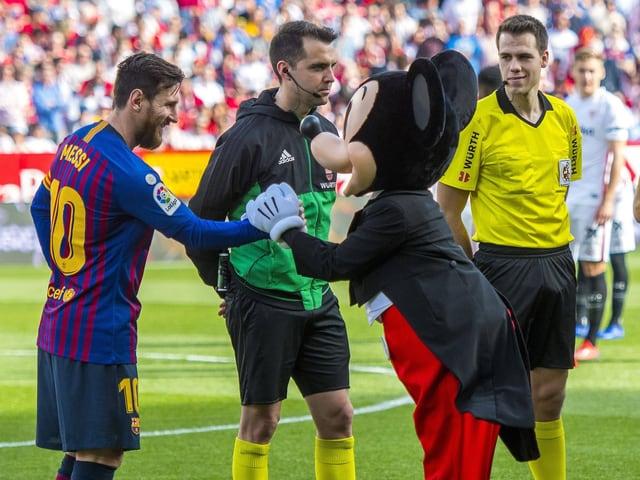 Lionel Messi schüttelt Mickey Mouse die Hand