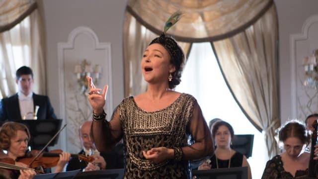 Marguerite singt mit Leidenschaft, im Hintergrund spielt ein Orchester.