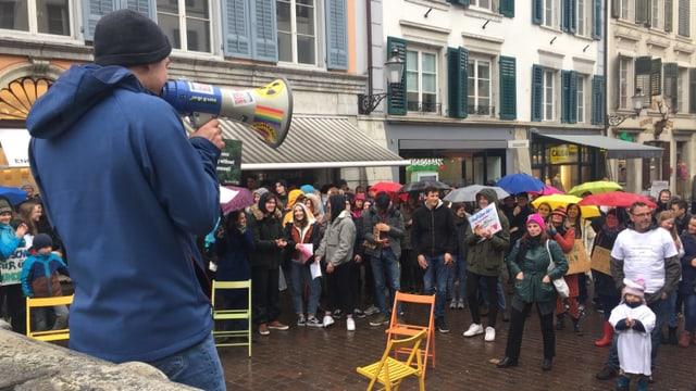 Ein Jugendlicher spricht über ein Megaphone zur Kundgebung.