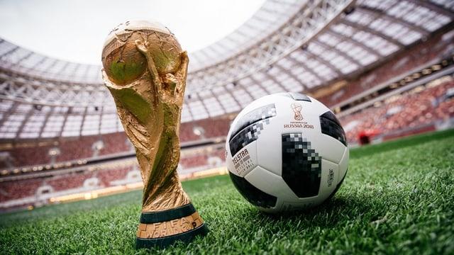 Der offizielle WM-Fussball von Adidas neben dem WM-Pokal.