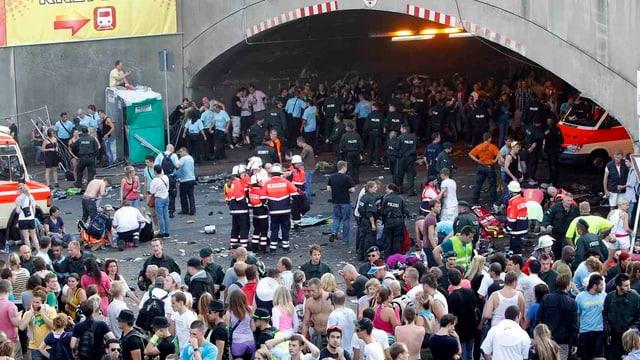 Blick in den Zugangsbereich der Loveparade mit dem Tunnel, in dem die Massenpanik stattfand: Viele Menschen stehen herum, in der Mitte Rettungssanitäter in roten Jacken.
