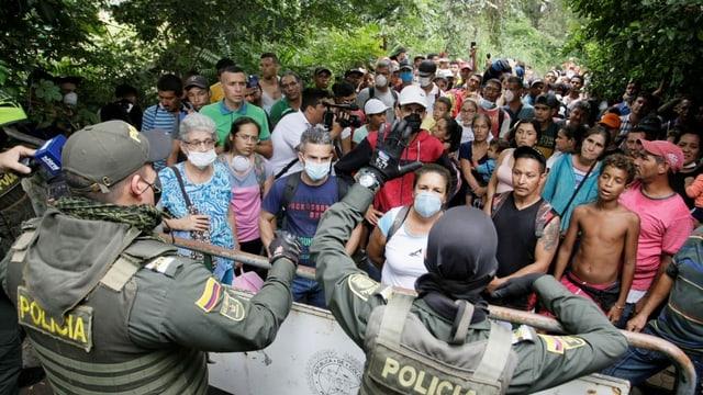 Das kolumbianische Militär hält Menschen zurück, die hinter einer Absperrung darauf warten, endlich nach Venezuela zurückkehren zu können.