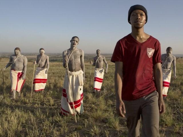 Ein Pfleger in T-Shirt und Jeans steht vor traditionell gekleideten Teilnehmern des Initiationsritus.