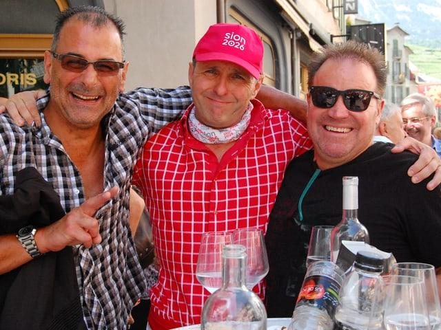 Befürworter mit Sion 2026-Kappe, flankiert von zwei lachenden Männern