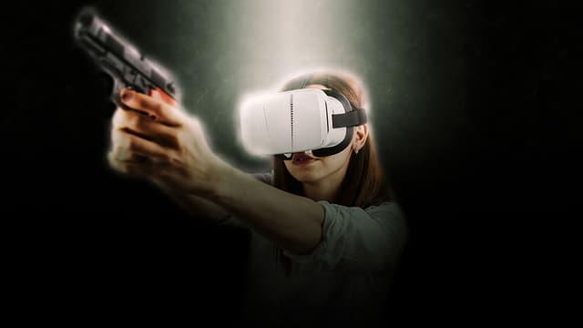 Frau mit einer VR-Brille im Gesicht hält eine Pistole in der Hand.